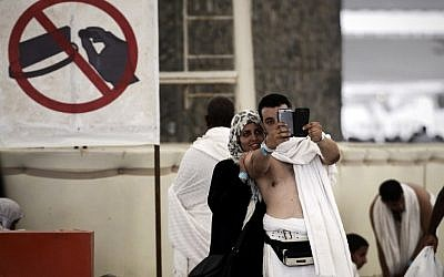 """Muslim pilgrims pose for a selfie during the """"Jamarat"""" ritual, the stoning of Satan, in Mina near the holy city of Mecca, on October 4, 2014. (photo credit: AFP/Mohammed al-Shaikh)"""