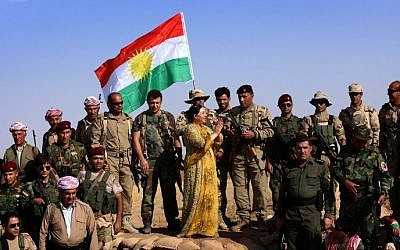 Turkish Kurdish singer Gulistan Perwer (C) performs for Kurdish Peshmerga fighters on the front line during the Muslim holiday of Eid al-Adha in the Gwer district, 40 kilometres south of Arbil, the capital of the Kurdish autonomous region in northern Iraq, on October 5, 2014. (photo credit: AFP Photo/Safin Hamed)