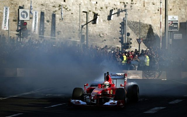 Three-time F1 Grand Prix winner Giancarlo Fisichella, of Italy, drives his Ferrari Formula 1 car below the ancient walls of Jerusalem's Old City on October 6, 2014, during the second Jerusalem F1 Peace Roadshow. (photo credit: AFP PHOTO / THOMAS COEX)