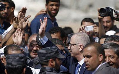 Palestinian Authority Prime Minister Rami Hamdallah (C) greets people during a visit to the Shejaiya neighborhood of Gaza City, October 9, 2014. (photo credit: Said Khatib/AFP)