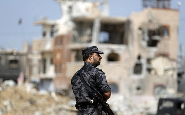 A Palestinian Hamas security officer stands guard as Palestinian Authority Prime Minister Rami Hamdallah (unseen) arrives to tour some of the areas worst hit by the 50-day war between Israel and Gaza militants in July and August, on October 9, 2014. (photo credit: Mohammed Abed/AFP)