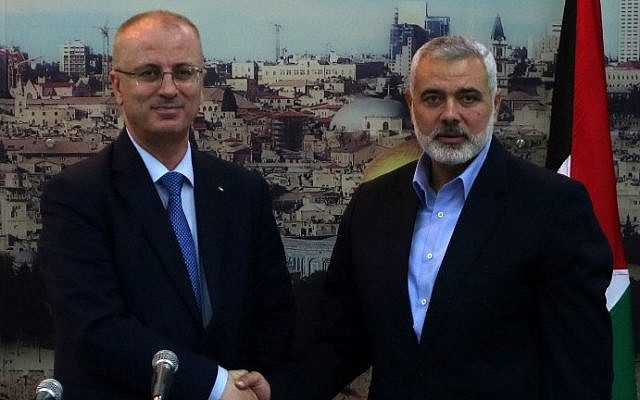 Hamas's former Gaza prime minister and leader, Ismail Haniyeh (right), shakes hands with Palestinian Authority Prime Minister Rami Hamdallah at Haniyeh's house in Gaza City, October 9, 2014. (photo credit: AFP/Said Khatib)