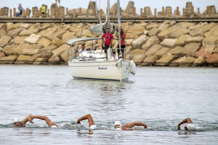 Israeli swimmers (from left to right) Ben Enosh, Luc Chetboun, 46, Ud Erel, 66, Ori Sela, 41, Doron Amosi, 45, Oded Rahav, 43, arrive in Israel after attempting to break the World record and the Guinness world record for longest swim in open sea and to raise awareness on sea protection, on October 11, 2014 in the Israeli coastal city of Herzliya. (photo credit: AFP/ JACK GUEZ)