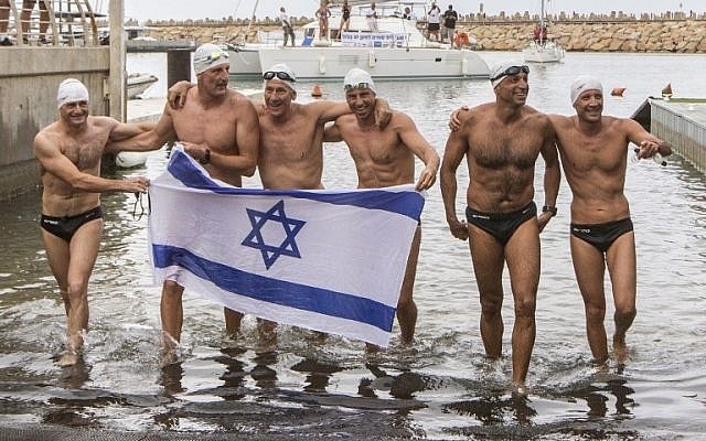 Israeli swimmers (from left to right) Ben Enosh, Luc Chetboun, 46, Ud Erel, 66, Ori Sela, 41, Doron Amosi, 45, Oded Rahav, 43, celebrate after swimming in turns 248 miles from the Mediterranean island of Cyprus to Israel in an attempt to break the World record and the Guinness world record for longest swim in open sea and to raise awareness on sea protection, on October 11, 2014 in the Israeli coastal city of Herzliya. (photo credit: AFP/ JACK GUEZ)