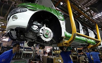 Iranian men work on a Peugeot 206 at the Iran Khodro auto plant, west of Tehran, on October 11, 2014. (AFP/Atta Kenare)