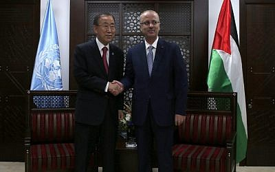 Palestinian prime minister Rami Hamdallah (R) shakes hands with UN Secretary-General Ban Ki-Moon following the latter's arrival in the West Bank city of Ramallah on October 13, 2014. (photo credit: AFP Photo/Ammar Awad)