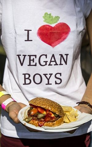 "A visitor holds a plate with a vegan hamburger during the ""Vegan Fest"" fair on October 13, 2014, Ramat Gan Israel. (photo credit: AFP/JACK GUEZ)"