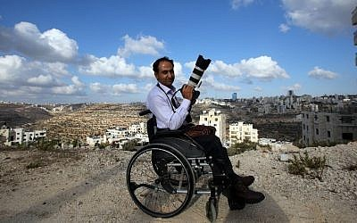 Palestinian photographer Osama Silwadi poses for a picture in the West Bank city of Ramallah on September 10, 2014. (photo credit: Abbas Momani/AFP)