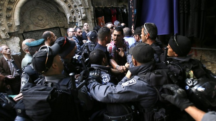 Israeli anti-riot policemen scuffle with Palestinian worshippers in Jerusalem's Old City on October 24, 2014. (Photo credit: AFP/GALI TIBBON)