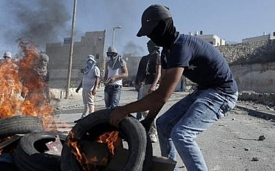 A Palestinian protester burns a tire during clashes with Israeli security officers in the Issawiya district of Arab east Jerusalem on October 24, 2014. (Photo credit: AFP / AHMAD GHARABLI)