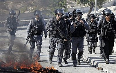 Israeli security officers run past burning tires during clashes with Palestinian protesters in the Issawiya neighborhood, in East Jerusalem on October 24, 2014. (Photo credit: AFP/ AHMAD GHARABLI)