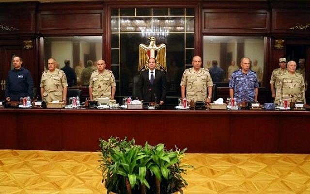 Egypt's President Abdel Fattah el-Sissi is flanked by members of the high military council as they observe a minute of silence for the soldiers who were killed in the Sinai Peninsula. October 25, 2014 (Photo credit: Egyptian Presidency/AFP)