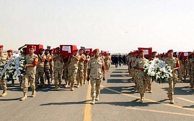 A handout picture released on October 25, 2014 by the Egyptian Presidency, shows the funeral for 30 solders killed the day before in the Sinai, at the Almaza military airbase in Cairo. (photo credit: AFP/ HO/EGYPTIAN PRESIDENCY)