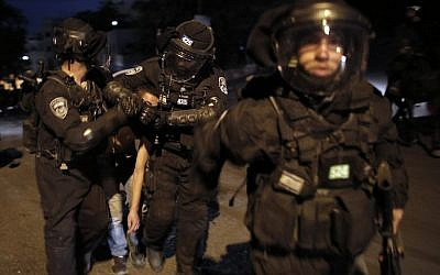 Israeli riot police officers detain a Palestinian youth during clashes in the East Jerusalem neighborhood of Silwan on October 26, 2014 (photo credit: AFP/AHMAD GHARABLI)
