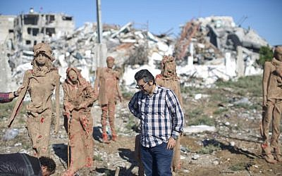 Palestinian artist Eyad Sabbah,40, stands in front of his statues standing amidst the rubble of buildings destroyed during the 50 days of conflict between Israel and Hamas last summer, in the Shejaiya neighborhood of Gaza City on October 21, 2014. (photo credit: AFP/MAHMUD HAMS)