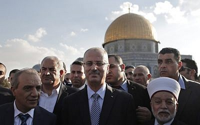 File: Palestinian Prime Minister Rami Hamdallah (center) stands next to the Mufti of Jerusalem Mohammed Hussein (right) outside Jerusalem's Dome of the Rock mosque on October 27, 2014. (AFP/Ahmad Gharabli)