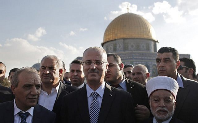 Palestinian Prime Minister Rami Hamdallah (C) stands next to the Mufti of Jerusalem Mohammed Hussein (R) outside Jerusalem's Dome of the Rock mosque on October 27, 2014.  (photo credit: AFP PHOTO / AHMAD GHARABLI)