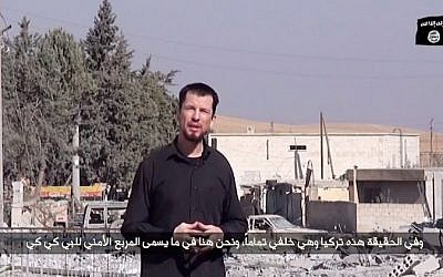 Screen capture from a video released by the Islamic State (IS) group on October 27, 2014 that purportedly shows kidnapped British reporter John Cantlie standing in war-damaged Kobani. (photo credit: AFP/Islamic State video via Youtube/HO)