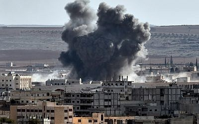 Smoke rises from an airstrike in the Syrian town of Ain al-Arab, known as Kobane by the Kurds, near the Turkish-Syrian border, seen from the southeastern village of Mursitpinar, Sanliurfa province, on October 9, 2014. (photo credit: AFP/ARIS MESSINIS)