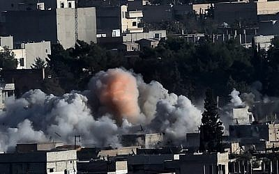 Smoke rises after strikes from the US-led coalition in the Syrian town of Kobani, on October 10, 2014 (Photo credit: Aris Messinis/AFP)