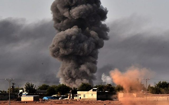 Smoke rises from the the Syrian town of Ayn al-Arab, known as Kobani by the Kurds, after a strike from the US-led coalition as it seen from the Turkish - Syrian border in the southeastern village of Mursitpinar, Sanliurfa province, on October 13, 2014. (Photo credit: AFP/ARIS MESSINIS)