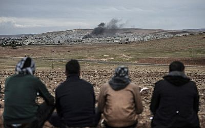Kurdish people watch the Syrian town of Kobani, from the Turkish side of the border on October 19, 2014.  (photo credit: AFP/BULENT KILIC)