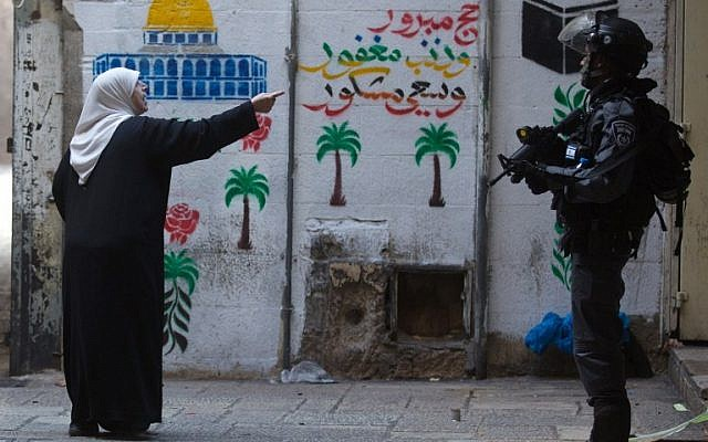 A Palestinian woman shouts at Israeli policemen in the old city of Jerusalem on October 30, 2014 after Israeli authorities temporarily closed the al-Aqsa mosque compound, Islam's third holiest site but also the most sacred place in Judaism. (photo credit: AFP/MENAHEM KAHANA)