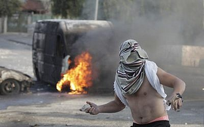A masked Palestinian throws a rock during clashes with Israeli security forces in East Jerusalem, October 30, 2014. (photo credit: AFP/Ahmad Gharabli)
