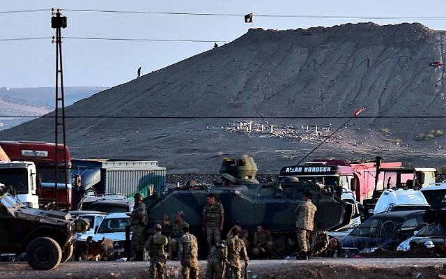 Islamic State (IS) militants (Rear) stand next to an IS flag atop a hill in the Syrian town of Ain al-Arab, known as Kobani by the Kurds, as seen from the Turkish-Syrian border, with Turkish troops in foreground, in the southeastern town of Suruc, Sanliurfa province, on October 6, 2014. (photo credit: AFP/ARIS MESSINIS)