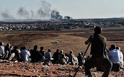 Kurdish people watch smoke billowing from Kobani as they gather upon a hill overlooking the Syrian town of Kobani, also known as Ain al-Arab, in the southeastern village of Mursitpinar, Sanliurfa province, on October 15, 2014.  (photo credit: AFP/ ARIS MESSINIS)