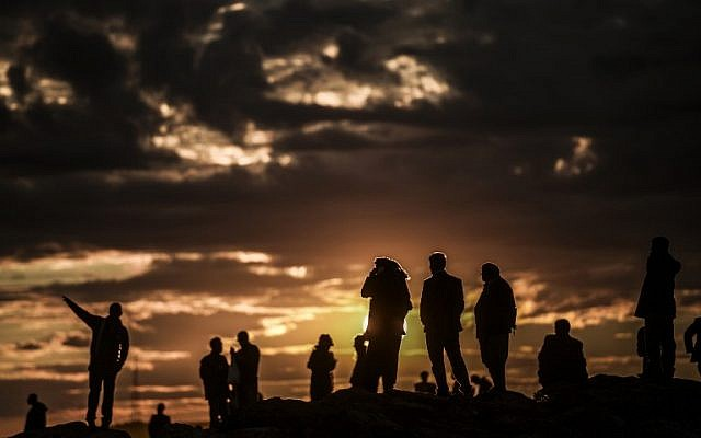 Kurdish people watch the Syrian town of Kobani, also known as Ain al-Arab, at sunset from the southeastern village of Mursitpinar, Sanliurfa province, on October 19, 2014. (photo credit: AFP PHOTO / BULENT KILIC)