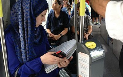 A Palestinian student reads her textbook on the light rail at Shuafat, Jerusalem, September 30, 2014 (photo credit: Elhanan Miller / Times of Israel)