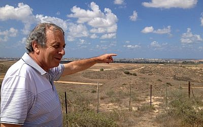 Kibbutz Nir Am resident Micha Ben Hillel points at Gaza from a mound outside his community (photo credit: Elhanan Miller/Times of Israel)
