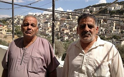 Elias Karaki (left) and his brother stand next to the house Nabil Karaki sold three months ago in Silwan, October 2, 2014. (photo credit: Elhanan Miller/Times of Israel)