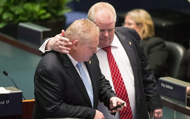 Rob Ford (right) talks to his brother Doug Ford in the Toronto council chamber, November, 2013 (photo credit: AP/The Canadian Press/ Chris Young)