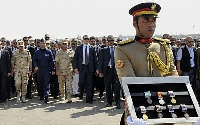 In this photo provided by Egypt's state news agency MENA, Egyptian President Abdel-Fattah el-Sissi, far left, and other officials follow a soldier carrying medals of troops killed in Friday's assault in the Sinai Peninsula, during a military funeral in Cairo, Egypt, Saturday, Oct. 25, 2014 [photo credit: AP/MENA)