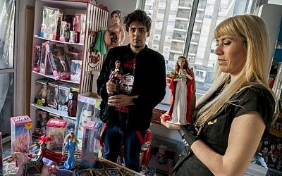 Artists Emiliano Paolini, left, and Marianela Perelli, pose for a photo while holding their Ken and Barbie dolls dressed as religious figures, in Rosario, Argentina, Friday, Oct. 10, 2014. Paolini and Perelli had planed to exhibit 33 unique pieces of the fashion dolls on Saturday. The provocative art exhibit that features the dolls as religious figures such as the Virgin Mary and her boyfriend Ken as a crucified Jesus Christ has been canceled amid complaints and threats by angry believers, creators of the collection said Friday. (photo credit: AP Photo/Marcelo Manera)