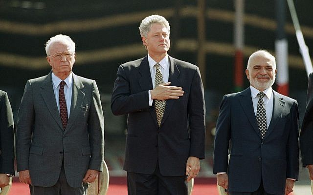 U.S. President Bill Clinton puts his hand on his heart, as he stands with Israeli Prime Minister Yitzhak Rabin, left, and Jordan's King Hussein while national anthems are played at the Israeli/Jordan peace signing ceremony at the Wadi Araba Israel/Jordan border crossing near Eilat in Israel on Wednesday, Oct. 26, 1994 (photo credit: AP/David Brauchli)