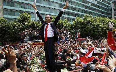 Indonesian President Joko Widodo gestures to the crowd during a street parade following his inauguration in Jakarta, Indonesia, Monday, Oct. 20, 2014. (photo credit: AP Photo/Achmad Ibraham)
