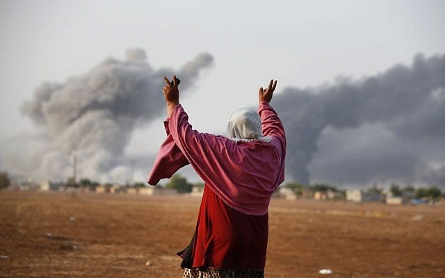 A Syrian Kurd gestures as thick smoke rises following an airstrike by the US-led coalition in Kobani, on Monday, October 13, 2014. (photo credit: AP Photo/Lefteris Pitarakis)