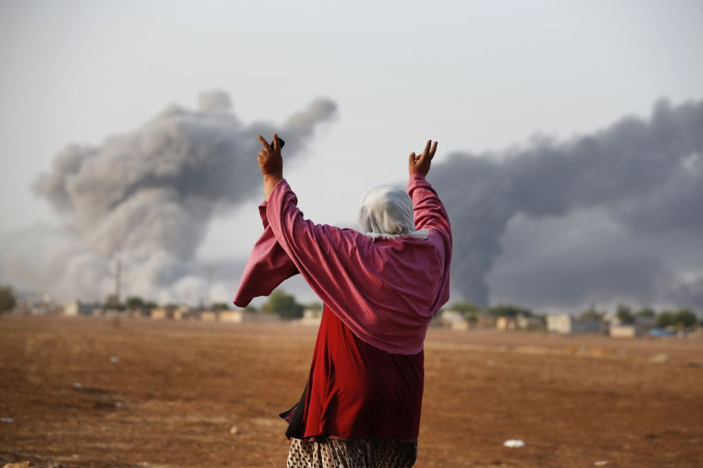 A Syrian Kurd gestures as thick smoke rises following an airstrike by the US-led coalition in Kobani, Syria as fighting continued between Syrian Kurds and Islamic State forces, on Monday, October 13, 2014. (photo credit: AP Photo/Lefteris Pitarakis)