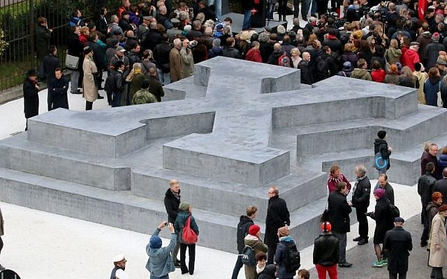 People surround a memorial dedicated to deserters of the Nazi Wehrmacht troops and victims of their military justice during its unveiling ceremony in downtown Vienna, Austria, Friday, October 24, 2014 (Photo credit: Ronald Zak/AP)