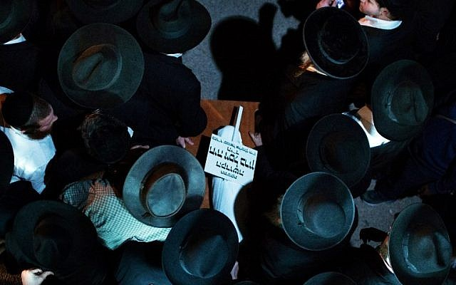 Ultra-Orthodox Jewish mourners carry the body of three-month-old Chaya Zissel Braun during her funeral in Jerusalem on October 23, 2014, after she was killed when a Palestinian driver rammed a group of pedestrians. (photo credit: AFP/ Menahem Kahana)