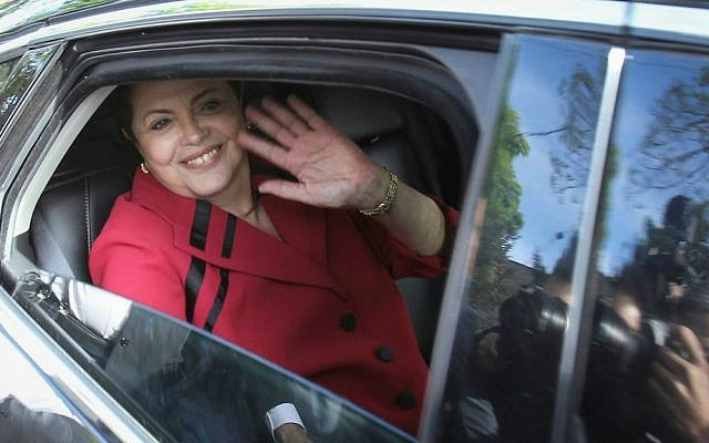 Brazil's President Dilma Rousseff, who is running for re-election with the Workers Party, PT, waves from a car after voting in general elections in Porto Alegre, Brazil, early Sunday, Oct. 5, 2014. (AP Photo/Nabor Goulart)