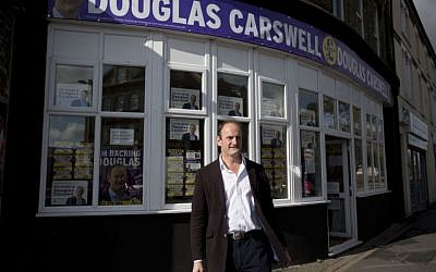 Douglas Carswell, the winning UK Independence Party (UKIP) candidate for the Clacton by-election, poses for photographs outside his campaign offices in Clacton-on-Sea, England, October 7, 2014.  (photo credit: AP Photo/Matt Dunham)