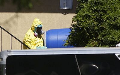 A hazardous material cleaner removes a blue barrel from the apartment in Dallas, Friday, Oct. 3, 2014, where Thomas Eric Duncan, the Ebola patient who traveled from Liberia to Dallas, stayed  (photo credit: AP Photo/LM Otero)