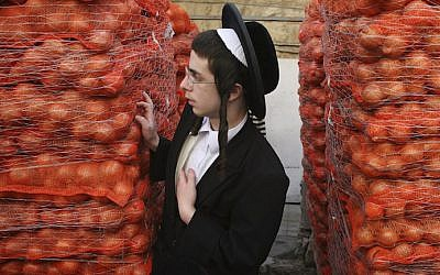 A haredi youth stands next to piles of potatoes in Jerusalem (Photo credit: Matanya Tausig/Flash90)