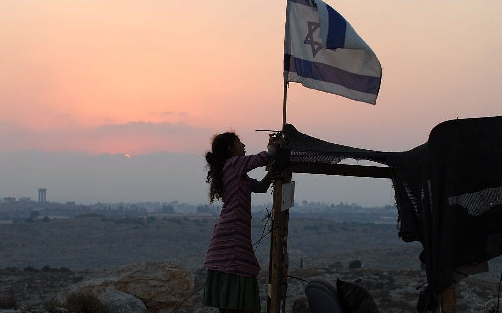 An Israeli girl raises an Israeli flag over a makeshift structure in the illegal outpost of Givat Tzuria near the settlement of Avnei Hefetz, located east of the West Bank Palestinian city of Tulkarem, in this 2009 photograph. (photo credit: Gili Yaari / FLASH90)