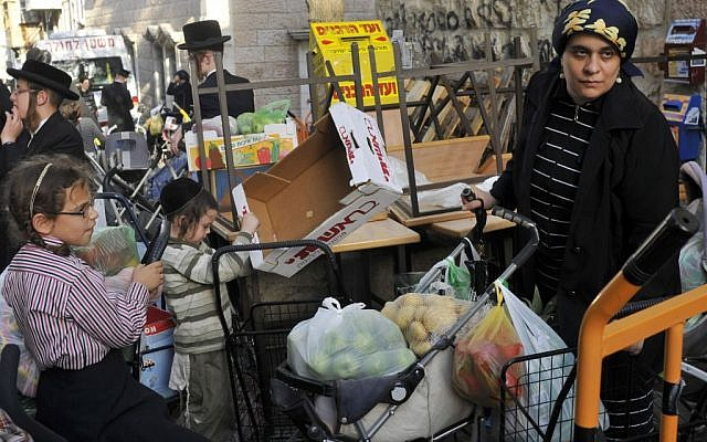 An ultra-Orthodox woman waits for food before the Sukkot holidays in the Mea Shearim market in Jerusalem.  (photo credit: Serge Attal / Flash 90