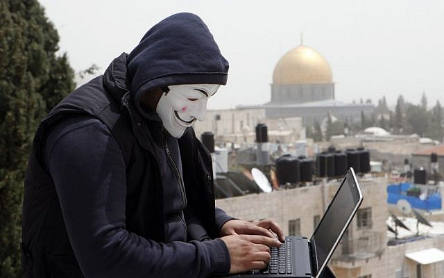 A Palestinian in a Guy Fawkes mask on a computer in Jerusalem, April 8, 2013. (photo credit: Sliman Khader/Flash90)